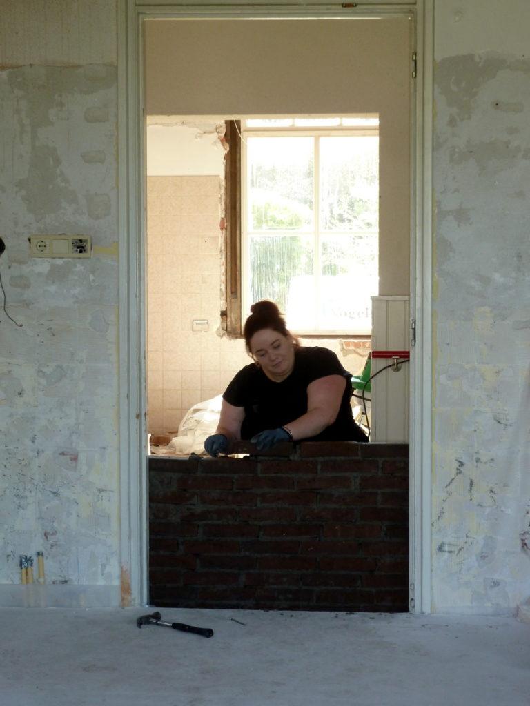 Anneke metselt eigenhandig een deur dicht